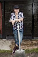 farmhand (female) - Portrait of confident female farmer with shovel standing against barn Stock Photo - Premium Royalty-Freenull, Code: 698-07439578