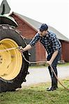 Full length mid adult man washing tractor wheel with hose in farm