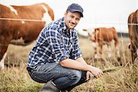 Portrait of farmer with grass crouching on field while animals grazing in background Stock Photo - Premium Royalty-Freenull, Code: 698-07439591