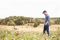 Side view of mid adult farmer walking on field Stock Photo - Premium Royalty-Freenull, Code: 698-07439596
