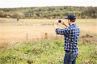Rear view of farmer photographing field through mobile phone Stock Photo - Premium Royalty-Freenull, Code: 698-07439597