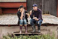 Full length of couple having breakfast on corrugated iron at farm Stock Photo - Premium Royalty-Freenull, Code: 698-07439601