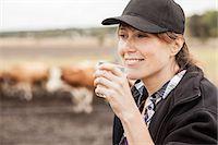 Mid adult female farmer drinking milk in farm Stock Photo - Premium Royalty-Freenull, Code: 698-07439602