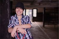 farmhand (female) - Portrait of happy female farmer with pitchfork standing at entrance of barn Stock Photo - Premium Royalty-Freenull, Code: 698-07439610