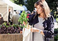 Young woman buying leaf vegetables at market Stock Photo - Premium Royalty-Freenull, Code: 698-07439646