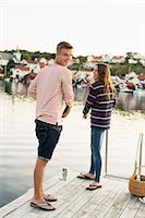 Rear view portrait of man with woman fishing on pier at lake Stock Photo - Premium Royalty-Freenull, Code: 698-07439687