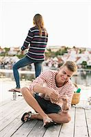 Happy man adjusting fishing rod while woman fishing in background at pier Stock Photo - Premium Royalty-Freenull, Code: 698-07439688