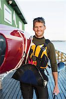 Portrait of confident man carrying kayak on shoulder at boathouse Stock Photo - Premium Royalty-Freenull, Code: 698-07439703