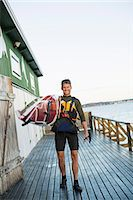 Full length portrait of happy man carrying kayak on shoulder at boathouse Stock Photo - Premium Royalty-Freenull, Code: 698-07439704