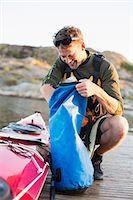 Happy man searching something in bag by kayak Stock Photo - Premium Royalty-Freenull, Code: 698-07439707