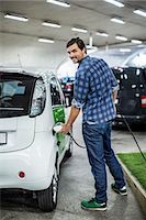 Full length portrait of young man charging electric car at gas station Stock Photo - Premium Royalty-Freenull, Code: 698-07439752