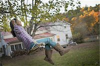 swing (sports) - A farmhouse garden, Autumn trees lit by late sunshine. A child seated on a swing. Stock Photo - Premium Royalty-Freenull, Code: 6118-07439804