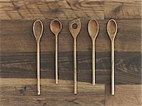 Home cooking. A wooden table with a varied wood grain and colour. Five wooden spoons in a row. Stock Photo - Premium Royalty-Freenull, Code: 6118-07439838