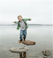 A day out at Ashokan lake. A boy jumping across stepping stones. Stock Photo - Premium Royalty-Freenull, Code: 6118-07440277