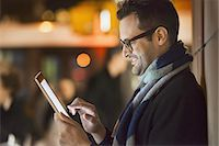 A man in a city at night, looking at a computer tablet. Stock Photo - Premium Royalty-Freenull, Code: 6118-07440408