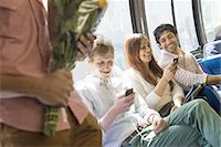 Urban Lifestyle. A group of people, men and women on a city bus, in New York city. Two people checking their phones. One man standing holding a bunch of flowers. Stock Photo - Premium Royalty-Freenull, Code: 6118-07440882