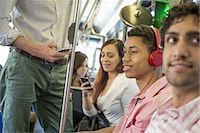 Urban Lifestyle. A group of people, men and women on a city bus, in New York city. A man with headphones on. A man and a woman checking their smart phones. Stock Photo - Premium Royalty-Freenull, Code: 6118-07440884