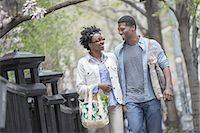 A couple walking in the park side by side carrying shopping bags. Stock Photo - Premium Royalty-Freenull, Code: 6118-07441042