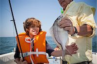 Boy and grandfather with caught fish on boat,  Falmouth, Massachusetts, USA Stock Photo - Premium Royalty-Freenull, Code: 614-07444057