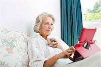 Senior woman using digital tablet while having coffee on bed at home Stock Photo - Premium Royalty-Freenull, Code: 693-07444520