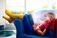 superhero costume - Little boy dressed as a super hero reading a book Stock Photo - Premium Royalty-Freenull, Code: 693-07444553