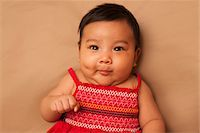 Close-up portrait of Asian baby lying on back, wearing red dress, looking at camera and making funny face, studio shot on brown background Stock Photo - Premium Royalty-Freenull, Code: 600-07453957