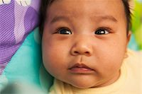 Close-up portrait of two month old Asian baby lying on back, studio shot Stock Photo - Premium Royalty-Freenull, Code: 600-07453959