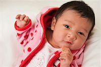 Close-up portrait of two week old Asian baby girl in pink polka dot jacket, smiling and looking at camera, studio shot Stock Photo - Premium Royalty-Freenull, Code: 600-07453964