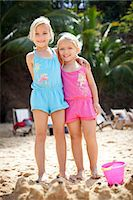 girls standing in front of sand castle on beach Stock Photo - Premium Royalty-Freenull, Code: 613-07454000