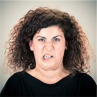 Young long curly hair lady grimacing portrait Stock Photo - Premium Royalty-Freenull, Code: 6106-07455206