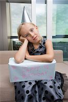 sad child sitting - Portrait of sad girl with birthday gift sitting on sofa at home Stock Photo - Premium Royalty-Freenull, Code: 693-07455870