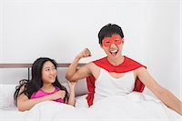 superhero - Portrait of excited man in superhero costume with woman on bed Stock Photo - Premium Royalty-Freenull, Code: 693-07455955