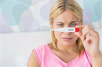 Close-up of sick woman taking temperature with thermometer in bed Stock Photo - Premium Royalty-Freenull, Code: 693-07456376
