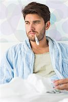 Sick man with thermometer in mouth sitting on bed Stock Photo - Premium Royalty-Freenull, Code: 693-07456406