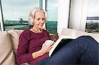Senior woman reading book on sofa at home Stock Photo - Premium Royalty-Freenull, Code: 693-07456435