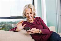 Happy senior woman text messaging through smart phone on sofa at home Stock Photo - Premium Royalty-Freenull, Code: 693-07456438