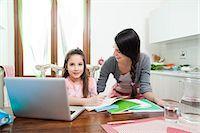 mum looking at daughter, laptop, homework, kitchen Stock Photo - Premium Royalty-Freenull, Code: 613-07458823