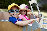 Boy and girl playing in a cardboard car Stock Photo - Premium Royalty-Freenull, Code: 613-07459154