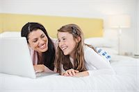 Mother and daughter using laptop in bedroom Stock Photo - Premium Royalty-Freenull, Code: 613-07459612