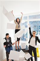 Three young businesswoman throwing papers mid air Stock Photo - Premium Royalty-Free, Artist: Blend Images, Code: 614-07486987