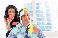 self adhesive note - Female office worker covering male colleague with sticky notes Stock Photo - Premium Royalty-Freenull, Code: 614-07487004