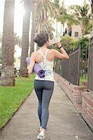 Young woman walking on sidewalk carrying yoga mat Stock Photo - Premium Royalty-Freenull, Code: 614-07487039