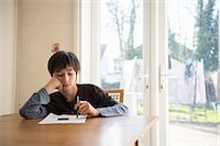 sad child sitting - Boy sitting at table, holding pen to paper Stock Photo - Premium Royalty-Freenull, Code: 614-07487228
