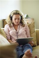 sole - Woman with headphones on sofa using digital tablet Stock Photo - Premium Royalty-Freenull, Code: 613-07492452