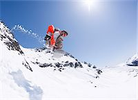 Young male snowboarder jumping on snowboard. Stock Photo - Premium Royalty-Freenull, Code: 613-07492680