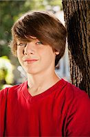 Teen boy leaning against a tree, portrait Stock Photo - Premium Royalty-Freenull, Code: 613-07492890