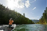 Woman fly fishing from drift boat on river. Stock Photo - Premium Royalty-Freenull, Code: 6106-07493801