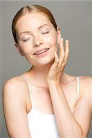 prevention - Young woman moisturizing face, eyes closed Stock Photo - Premium Royalty-Freenull, Code: 632-07494934