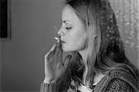 Beautiful woman smoking cigarette in black and white Stock Photo - Premium Royalty-Freenull, Code: 6109-07496971