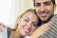 Nice young couple cuddling on couch smiling at the camera Stock Photo - Premium Royalty-Freenull, Code: 6109-07497350